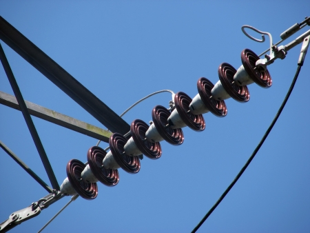 isolator high voltage: Telephoto view of insulators on an electrical pylon