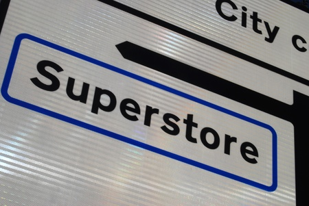 superstore: Closeup of traffic sign directing to city superstore. Stock Photo