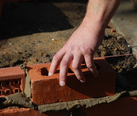 Close up of construction workers hand pressing brick into place. Stock Photo
