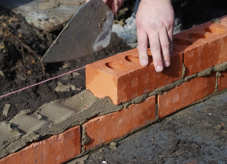 construction level: Construction worker laying bricks showing trowel and guideline.