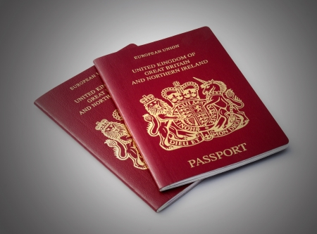 Two United Kingdom passports over plain background