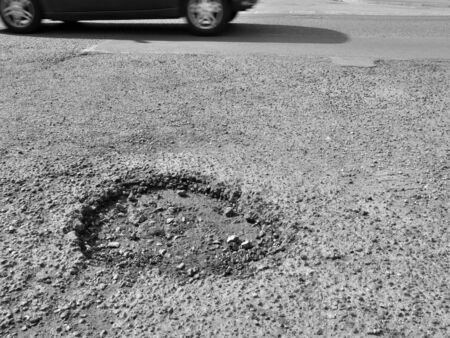 Motorcar drives past a pothole in road photo
