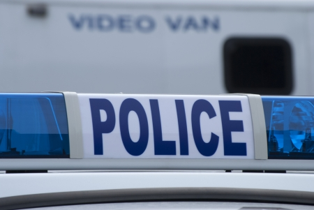 police: Closeup of police car sign with video unit vehicle in background. Stock Photo