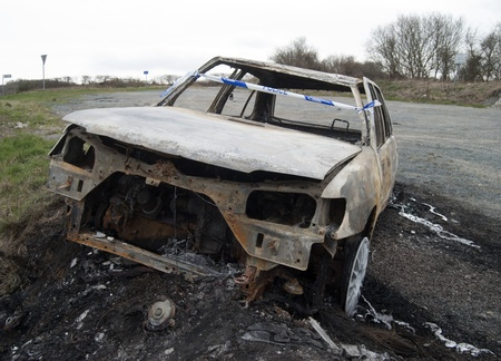 Burnt out abandoned car on the side of an isolated road  photo