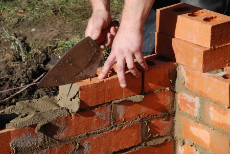 Closeup of bricklayer building a house extension  Photo shows man holding trowel while laying bricks  Stock Photo