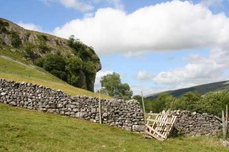 Yorkshire Dales: View of dry stone wall and broken gate in field in Yorkshire Dales Stock Photo