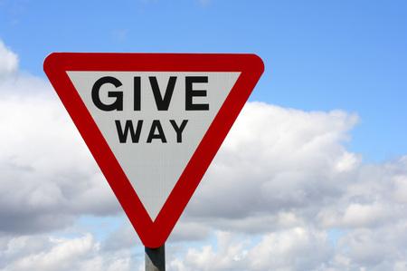 Horizontale foto van UK Give Way teken met bewolkte hemel