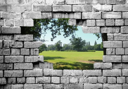 crumbling: Section of a crumbling brickwall with countryside view filling hole  Stock Photo
