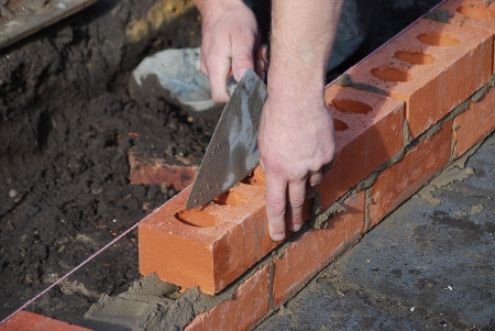 cement pile: Bricklayer using trowel to tap a brick level