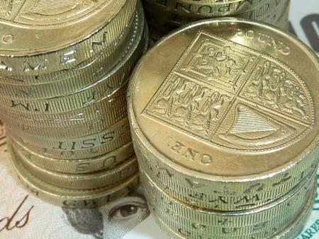 pound coins: Piles of UK pound coins on 10 pound banknote Stock Photo