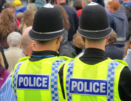 british man: Two British policemen watching during crowded street event