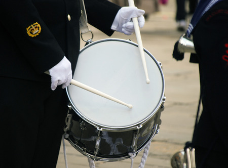warrant: Closeup of military musician playing drum in city center