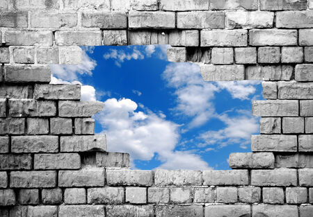 ancient prison: New life: Grey crumbling brickwall with cutout showing blue sky beyond Stock Photo