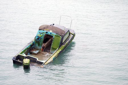 sunk: Lonely half sunk abandoned boat in middle of river