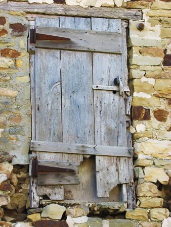 view of a wooden doorway: Closeup of neglected door in an abandoned stone building