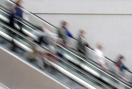 crowded space: People travelling on escalator taking with slow shutter speed to show movement Stock Photo