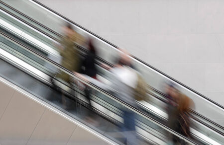 People travelling on escalator taking with slow shutter speed to show movement photo