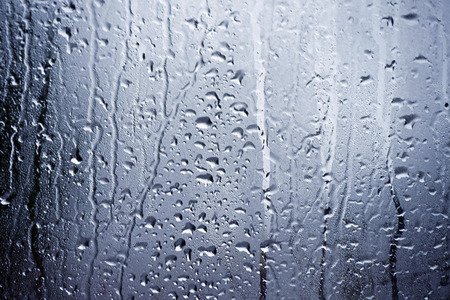 Rain water and condensation clings to window Stockfoto