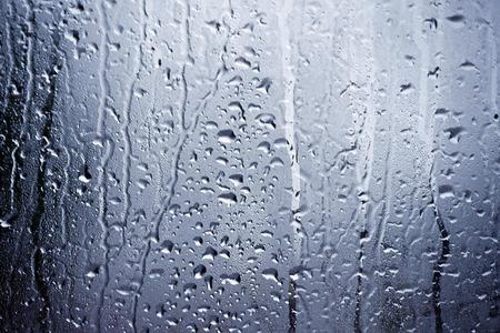 Regenwater en condens zich vastklampt aan het venster