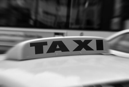 light zoom: Close up of TAXI sign with passing bus behind. Zoom effect applied on sign