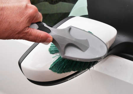 Man holding brush to clean car mirror photo