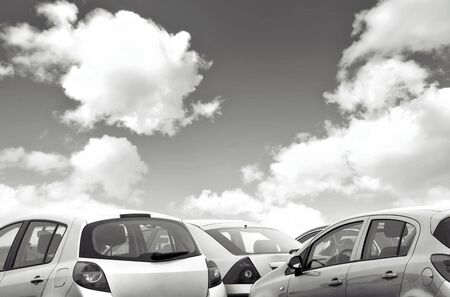 parked: Closeup view of parked cars with coudy sky in black and white