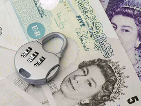 uk: Combination padlock rests on British banknotes