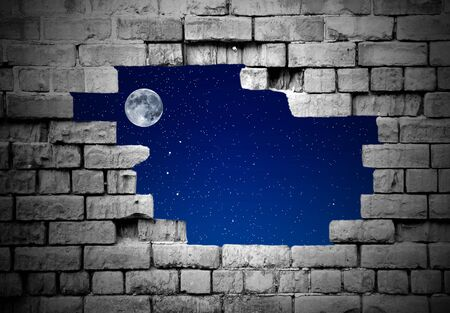 crumbling: Section of a crumbling brickwall with hole revealing stars and moon Stock Photo