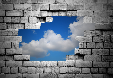 Section of a crumbling brick wall with hole revealing blue sky with clouds