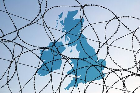 Conceptual image showing map of UK behind barbed wire barrier. Currently the UK has imposed restrictions on immigration to the UK.