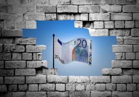 A hole in a crumbling brickwall revealing a twenty euro banknote