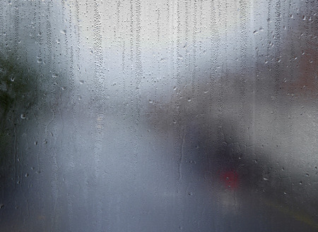 Water drops on steamed up window overlooking urban road