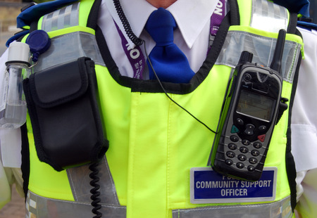 british: Closeup of a community support officer patrolling city streets.