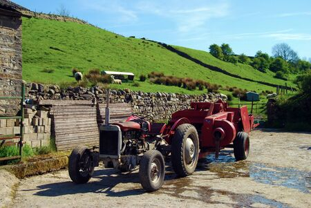 farmyard: Old tractor is parked in farmyard with sheep on hill in background