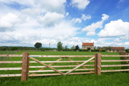 surrounds: Farmers fence surrounds grass area with farm in background Stock Photo