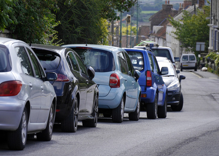 Row of parked cars in street in town centre