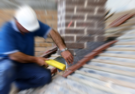 Trainee roofer installing lead flashing around chimney. Zoom effect added for effect