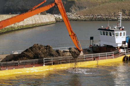 Dredging ship scooping soil from River Esk in Whitby