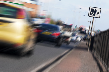 Zoom effect applied to speed camera sign on busy city road