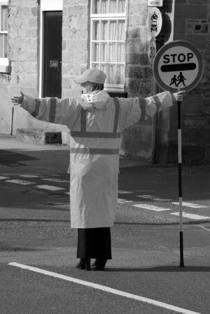 traffic warden: School crossing patrol officer halts traffic in UK urban area.
