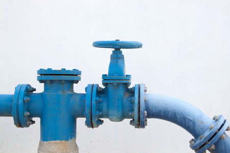 Large water supply valve with a white background of the cement wall