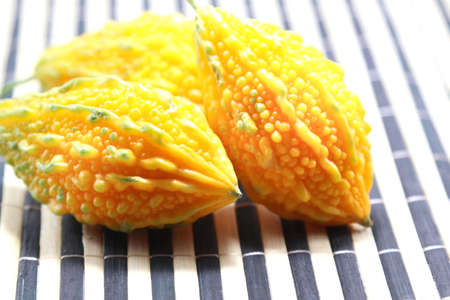 Yellow rough-skinned bitter gourd is ripe, edible and herbal, with a bitter taste on a white background.