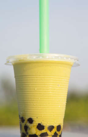 Smoothie, green tea and pearls in a ready-to-drink glass with ice, milk, sugar, then enjoy and cool off on a hot day against a blue sky background.
