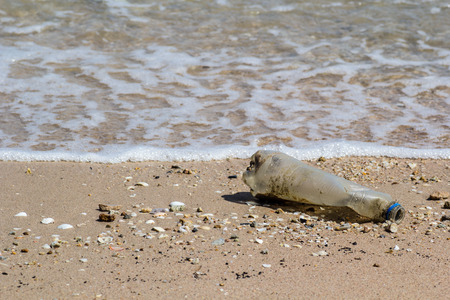 very dirty: This is a Garbage bottle on the beach with the sea. It is very dirty. Stock Photo