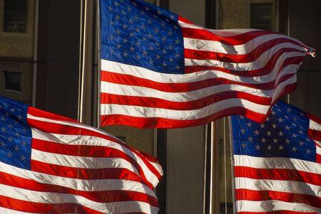 buiding: 3 american flags against buiding