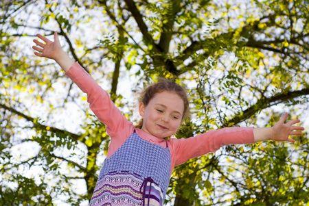 girl at playground, balancing on beam, looking at up, treessky behind