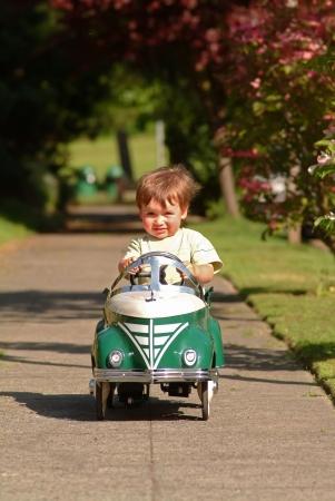 play boy: boy driving pedal car