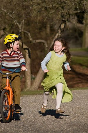 niño en bicicleta, niña corriendo junto a él Foto de archivo - 4111709