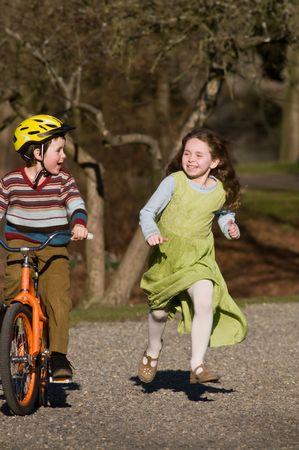 ni�o en bicicleta, ni�a corriendo junto a �l Foto de archivo - 4111709
