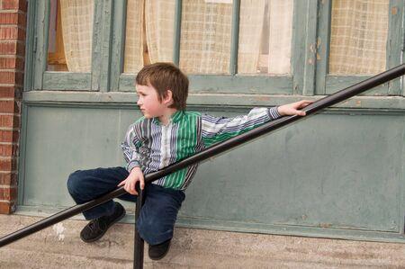 boy holding onto stair railing Stok Fotoğraf